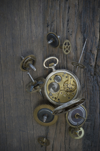 Old pocket watch and cogwheels on dark woodの写真素材 [FYI04336243]