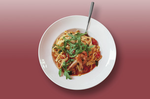 Tagliatelle with fried scampis, tomato sauce and rocket salaの写真素材 [FYI04336293]
