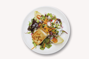 Close up of goat cheese au gratin with mixed salad on whiteの写真素材 [FYI04336298]
