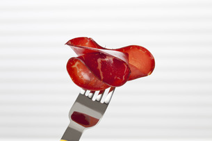 Slice of smoked beef on fork, close upの写真素材 [FYI04336357]