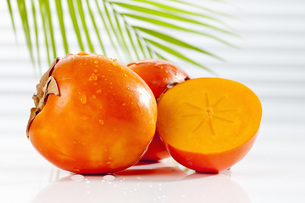 Kaki Persimmon with palm leaf, close upの写真素材 [FYI04336362]