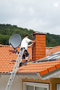 Europe, Germany, Rhineland Palatinate, Man covering chimneyの写真素材 [FYI04336367]