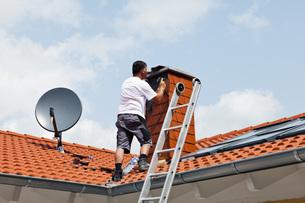 Europe, Germany, Rhineland Palatinate, Man covering chimneyの写真素材 [FYI04336370]