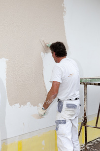 Europe, Germany, Rhineland Palatinate, Man plastering houseの写真素材 [FYI04336373]