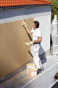 Europe, Germany, Rhineland Palatinate, Man plastering houseの写真素材 [FYI04336393]
