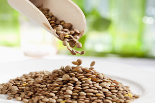 Lentils pouring from wooden scoop, close upの写真素材 [FYI04336395]