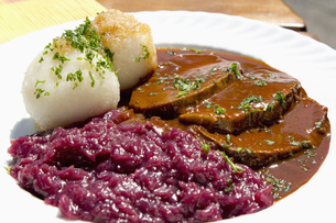 Plate of sauerbraten marinated beef with red cabbage and potの写真素材 [FYI04336399]