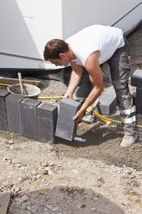 Germany, Rhineland Palatinate, Worker laying paving stones iの写真素材 [FYI04336401]