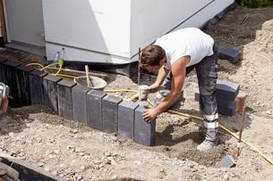 Germany, Rhineland Palatinate, Worker laying paving stones iの写真素材 [FYI04336402]