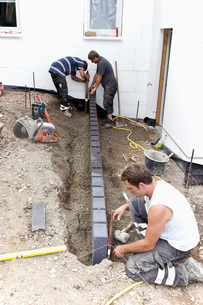 Germany, Rhineland Palatinate, Workers laying paving stonesの写真素材 [FYI04336403]