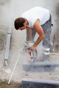 Germany, Rhineland Palatinate, Worker cutting paving stone wの写真素材 [FYI04336405]