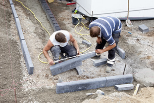 Germany, Rhineland Palatinate, Workers laying paving stonesの写真素材 [FYI04336406]