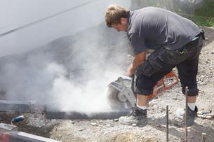 Germany, Rhineland Palatinate, Worker cutting paving stone wの写真素材 [FYI04336407]