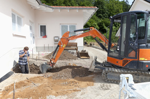 Germany, Rhineland Palatinate, Worker digging soil with excaの写真素材 [FYI04336408]
