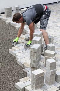 Germany, Rhineland Palatinate, Young man assembling paving sの写真素材 [FYI04336415]