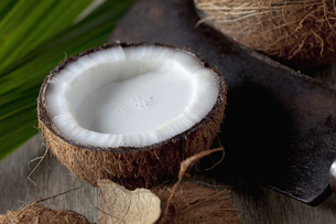 Half coconut with coconut milk and sickle, close upの写真素材 [FYI04336424]