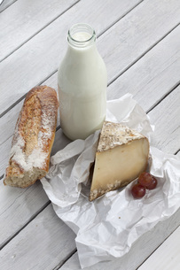 Sheep cheese, milk and bread on wooden tableの写真素材 [FYI04336442]