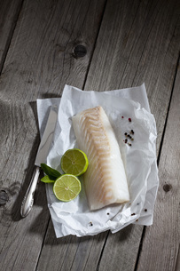 Filet of codfisch, lime and knife, and peppercorns on greaseの写真素材 [FYI04336461]
