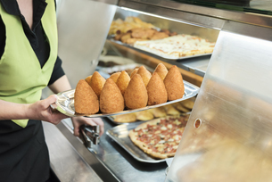 Woman serving fresh arancini, rice croquettes on plateの写真素材 [FYI04336493]