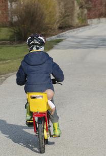 Austria, Boy cycling with doll on seatの写真素材 [FYI04336498]
