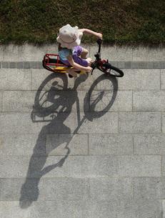 Austria, Girl cycling on streetの写真素材 [FYI04336503]