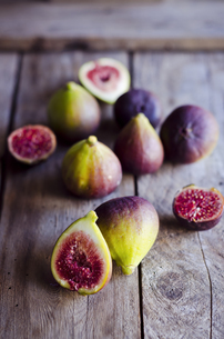 Whole and sliced fresh figs on wooden tableの写真素材 [FYI04336511]