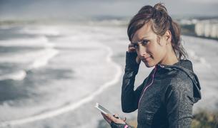 Portrait of mid adult sportive woman using smart phoneの写真素材 [FYI04336530]