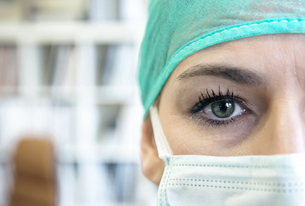 Close-up portrait of doctor wearing mask and surgical capの写真素材 [FYI04336531]