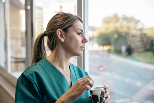 Woman in scrubs having coffee break looking out of the windoの写真素材 [FYI04336532]