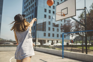 Young woman aiming at basketball hoopの写真素材 [FYI04336548]