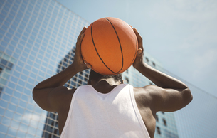 Young man holding basketball behind his headの写真素材 [FYI04336553]