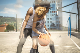 Young couple playing basketball on courtの写真素材 [FYI04336554]