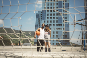 Young couple standing on basketball field, looking at cameraの写真素材 [FYI04336555]