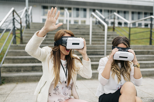 Two women having fun with VR glasses sitting outdoorsの写真素材 [FYI04336559]