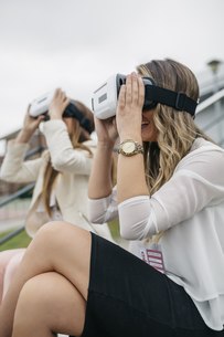 Two women having fun with VR glasses sitting outdoorsの写真素材 [FYI04336560]