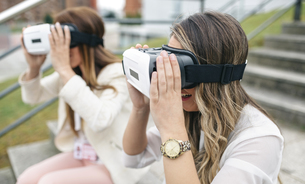 Two women having fun with VR glasses sitting outdoorsの写真素材 [FYI04336561]