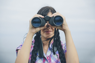 Woman looking through binocularの写真素材 [FYI04336564]