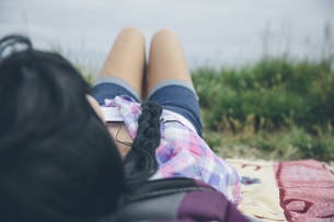 Back view of woman with braid lying on blanket on a meadowの写真素材 [FYI04336565]