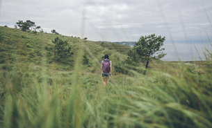 Spain, Asturias, back view of woman with backpack hiking onの写真素材 [FYI04336566]