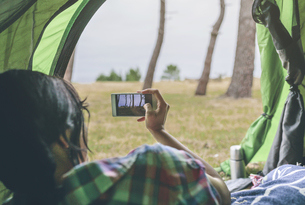 Back view of young woman with smartphone lying in a tent takの写真素材 [FYI04336569]