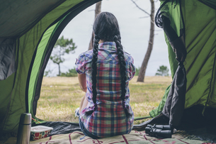 Back view of young woman sitting in a tent looking at distanの写真素材 [FYI04336570]