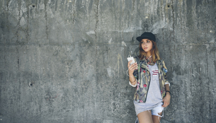 Young woman leaning against concrete wall listening music wiの写真素材 [FYI04336573]