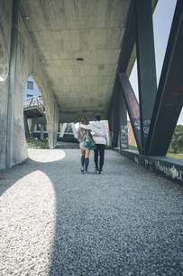 Back view of young couple in love walking arm in armの写真素材 [FYI04336576]
