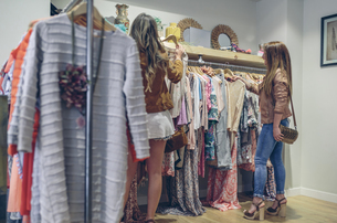 Two women shopping for clothes in a boutiqueの写真素材 [FYI04336585]