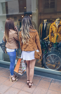 Two women holding shopping bags looking at shop windowの写真素材 [FYI04336590]