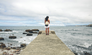 Back view of woman standing on pier looking at distanceの写真素材 [FYI04336605]