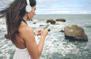 Woman listening music with headphones and smartphone in fronの写真素材 [FYI04336610]