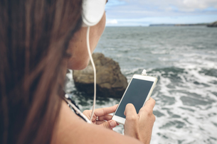 Woman using smartphone while listening with headphones in frの写真素材 [FYI04336611]