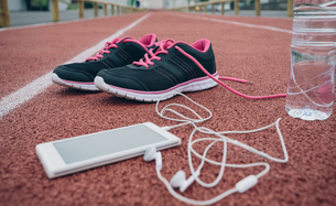 Sport shoes, smartphone with earbuds and bottle of water onの写真素材 [FYI04336615]