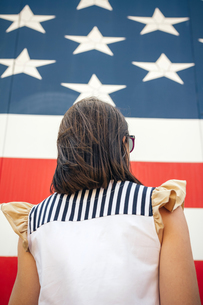 USA, back view of woman in front of Stars And Stripesの写真素材 [FYI04336622]